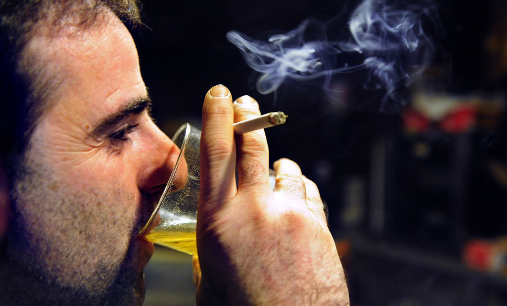 A man drinks beer while smoking a cigarette