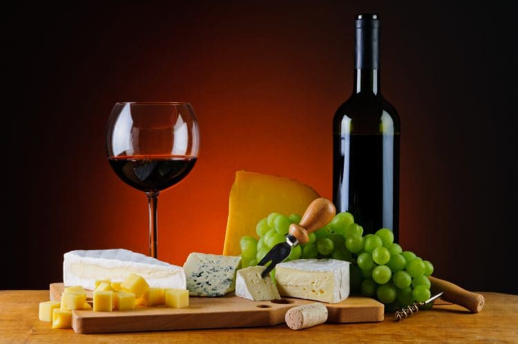 Bottle of red wine, cheese and grapes