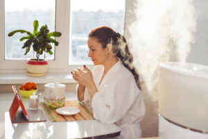 woman using a humidifier and drinking tea